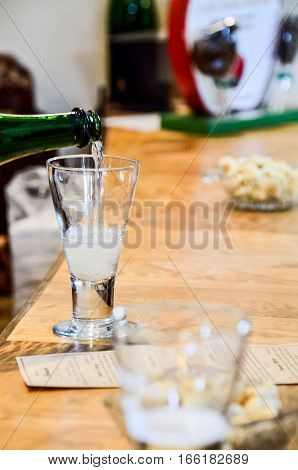 Pouring cider in glass at tasting room with crackers at bar