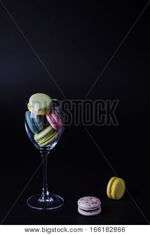delicious French dessert macarons flying out from the glass on a black background