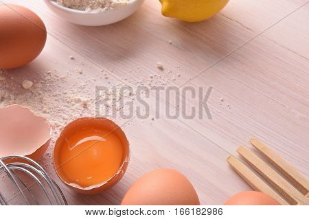 Fresh Eggs Flour And Lemon With Utensils On Bench Top