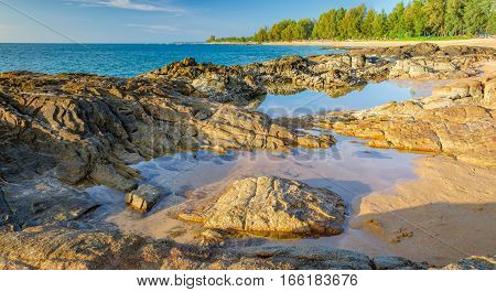 Beautiful seascape with sea rock and a strip of white sand of Nang Thong Beach, Khao Lak, Thailand. View of bright blue sea with protruding stones. Nature composition.