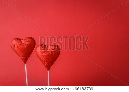 chocolate hearts shaped isolated on red background with copy space
