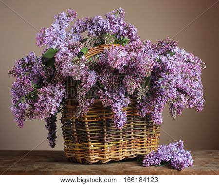 purple lilac in a basket on the table. still life with a bouquet of blooming lilacs.