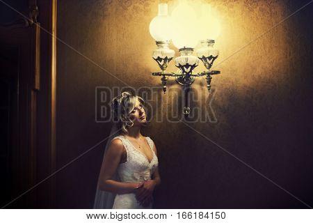 Thoughtful Bride Stands Under The Old Vintage Chandelier