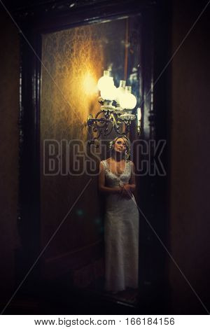 The Reflection Of Bride Standing In The Darkness Under The Vintage Chandelier