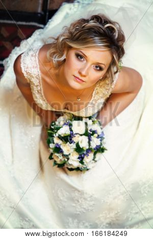 Pretty Bride Looks Up Thoughtful Holding A Bouquet Of Roses And Violets