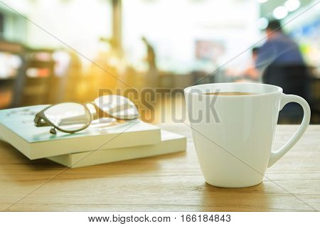 Cup Of Coffee, Eyeglass And Book On Wooden Table.