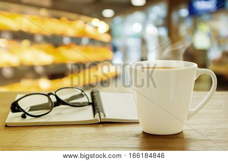 Cup Of Coffee And Note Book On Wooden Table. Coffee Break In Morning.