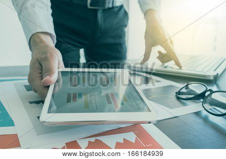 Businessman Working With Digital Tablet And Laptop With Financial Business Document.