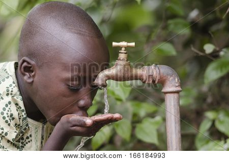 Water scarcity in the world symbol. African boy begging for water. In places like sub-Saharan Africa time lost to gather water and suffering from water-borne diseases is limiting people's lives.