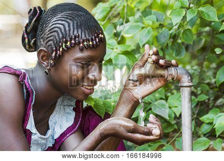 Happy African Schoolgirl Enjoying Clean Water from a Tap in Bamako Mali