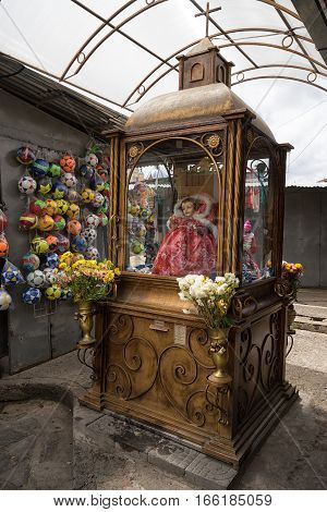July 10, 2016 Cuenca, Ecuador: a small brass vintage religious monument n the artisan market with plastic balls hanging on the vendor's booth wall in the background