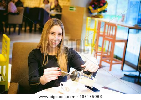 Woman In A Cafe. Young Girl In A Black Dress Sits At A Table, Pouring A Cup Of Ginger Tea