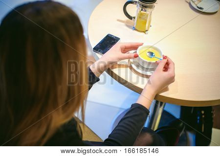 Woman In A Cafe. Young Girl In A Black Dress Sits At A Table, Stirring A Cup Of Ginger Tea