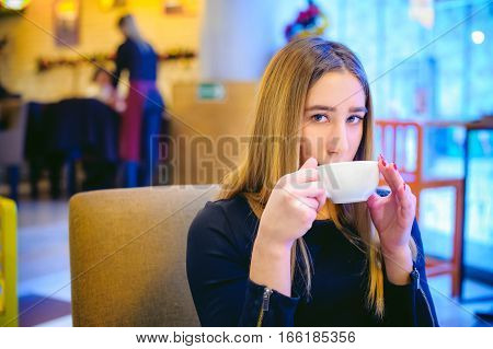 Woman In A Cafe. Young Girl In A Black Dress Sits At A Table, Drinking Tea From A Cup