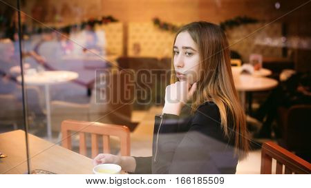 Woman Behind Window In Cafe. Young Girl In Black Dress Sits At Table, Holding  Beverage Cup
