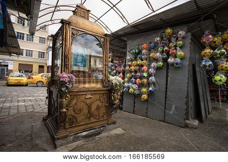 July 10, 2016 Cuenca, Ecuador: a small vintage religious monument in the artisan market with plastic balls hanging on the vendor's booth wall in the background