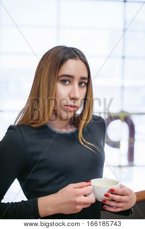 Young Woman In A Black Dress Holding In Hands A Cup Of Drink