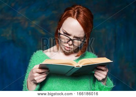 beautiful red-haired girl in a green sweater and glasses reading a book over magic dark blue background