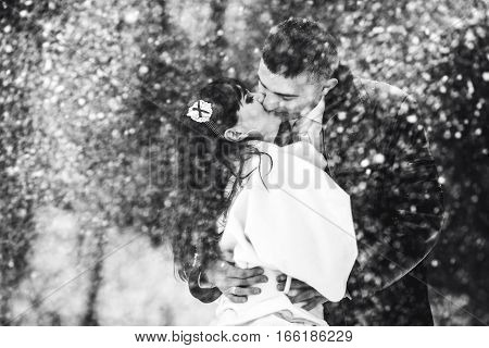 A Wedding Couple Kisses Tender In A Snow Flurry