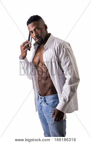 African American bodybuilder man, talking on cell phonewearing jeans and open shirt on naked muscular torso, isolated on white background