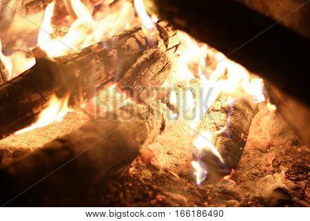 Burning big log fire in night fireplace. Closeup flame. Barbecue coal blazing