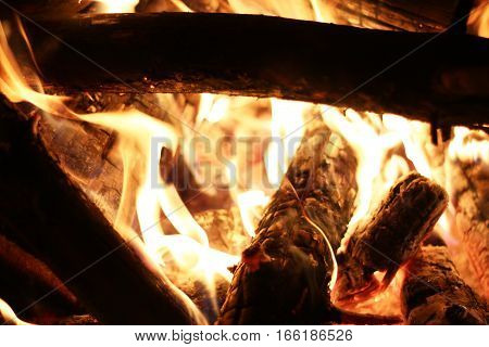 Closeup log fire in night fireplace. Burning flame. Barbecue coal blazing