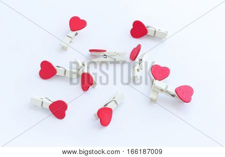 wooden clothes pin or cloth pegs with heart shape design on a white background for valentine concept