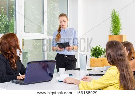 Pretty young business woman giving a presentation in a conference or meeting setting. People and teamwork concept - happy creative team in office. Women in businness
