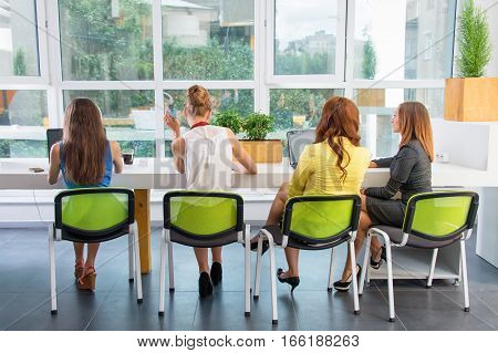 Group of pretty businesswoman working together with new startup project using laptop computer in modern loft, back view. People and teamwork concept - happy creative team in office. Women in businness