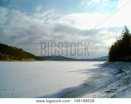 Photo of a frozen lake under a cloudy sky