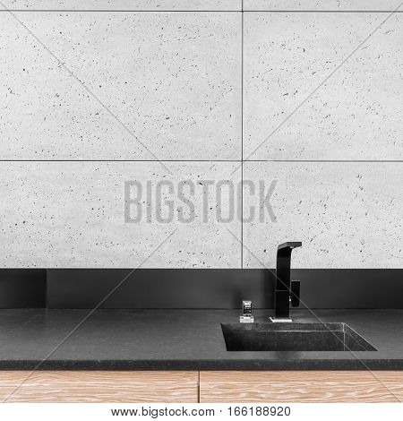 Modern kitchen with grey wall tiles black worktop sink and tap