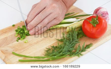 Closeup man's hand with a knife cut green onion on a wodden board.