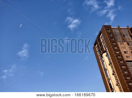 The exterior of modern buildings under a waning moon on the island of Macau China on a sunny morning as a jet flys by.