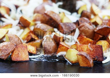 Frying ruddy potato and onion in sunflower oil on big pan. Cooking potatoes