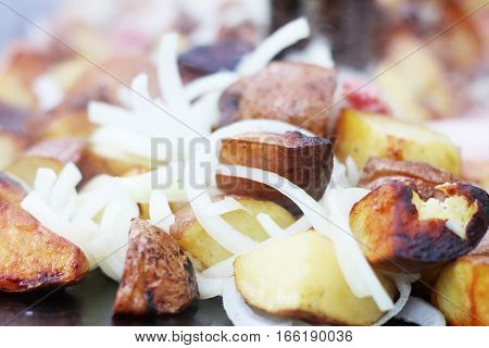 Frying potato and onion in sunflower oil on big pan. Cooking potatoes closeup