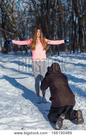 Photograper taking a shot of young woman with dumbbells in winter park