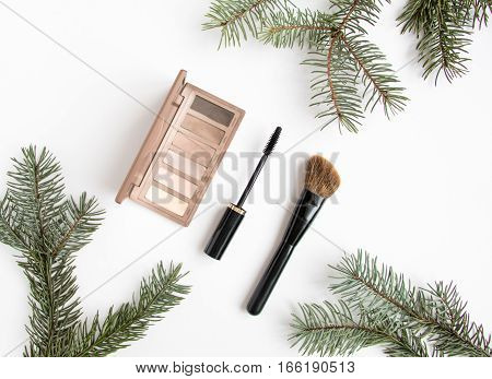 Winter cosmetics collage decorated with fir tree branches on white background. Eye shadows mascara and brush make up composition. Flat lay top view