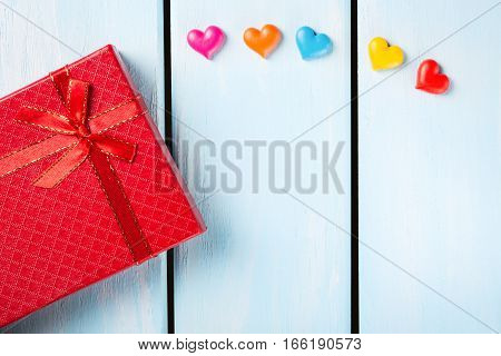 Red gift box with decorative hearts on nice blue wooden background with free space.