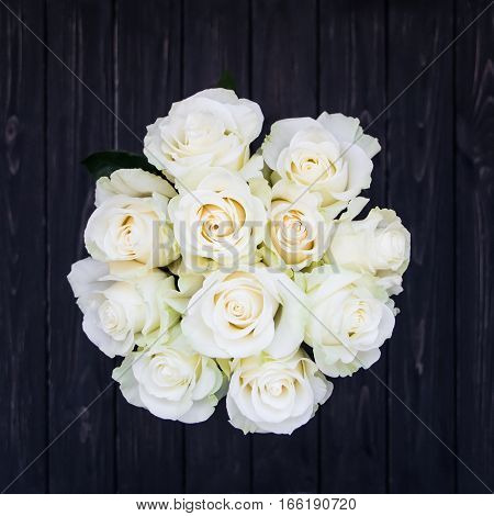 Perfect bouquet of creme luxury roses for wedding birthday or Valentine's day. Black old wooden background top view flat lay