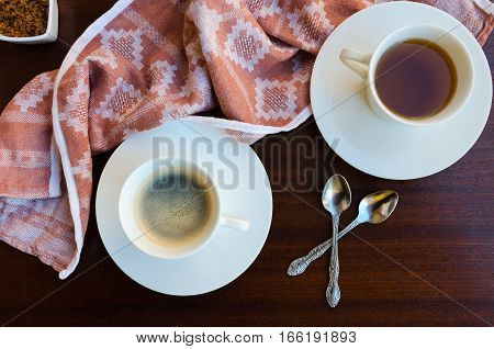 Cup of black tea and cup of coffee with teaspoons and napkin on wooden background. Common caffeinated drinks. Popular beverages concept. Top view.