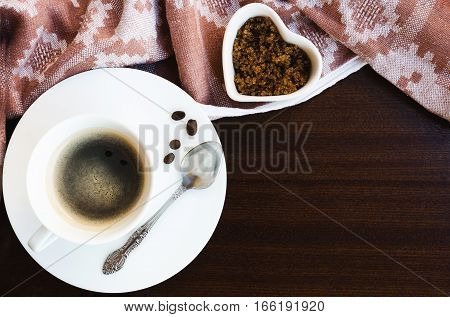 Cup of black coffee with coffee spoon brown sugar and vintage napkin on wooden background. Copy space.