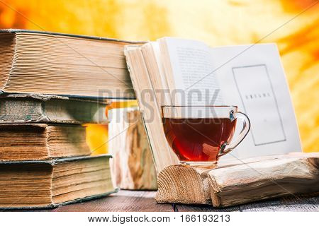Cup of tea on rustic wood board. Stack of old books next to tea. Open book on fire light background