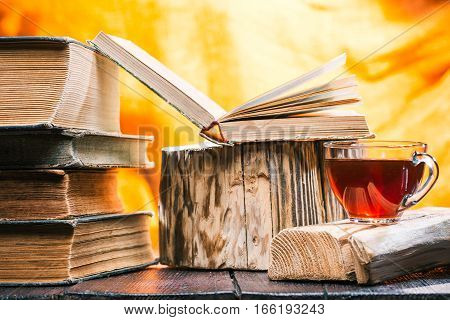 Cup of tea on rustic wood board. Stack of old books next to tea. Open book on wooden stand