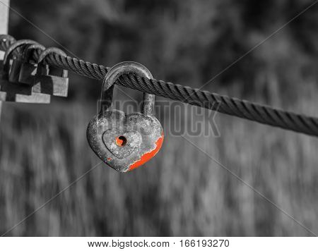 Heart shaped padlock with peeled off red paint in enlarged view and other old rusty padlocks as symbol of eternal love hanging on metal cable in black and white composition. Romance concept. Blurred background.