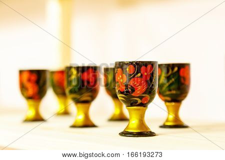 Wine Glasses Decorated With Ornaments In The Style Of Russian Khokhloma Standing On A Wooden Shelf.