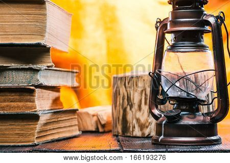 Books stack on wood. Kerosene lamp next to them and stand of stamp behind them