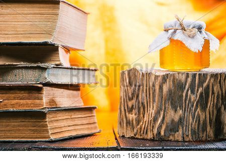 Honey in little glass jar on rustic wood stand. Stack of old books next to honey