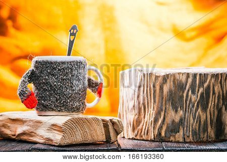 Teacup wearing wool sweater on wood stand. Smiling teaspoon inside