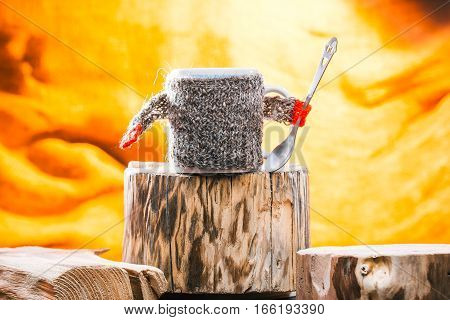 Teacup wearing wool sweater on wood stand. Fire light background