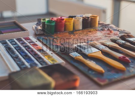 Palette with oil paints and gouache set. Clean painter workplace ready for drawing